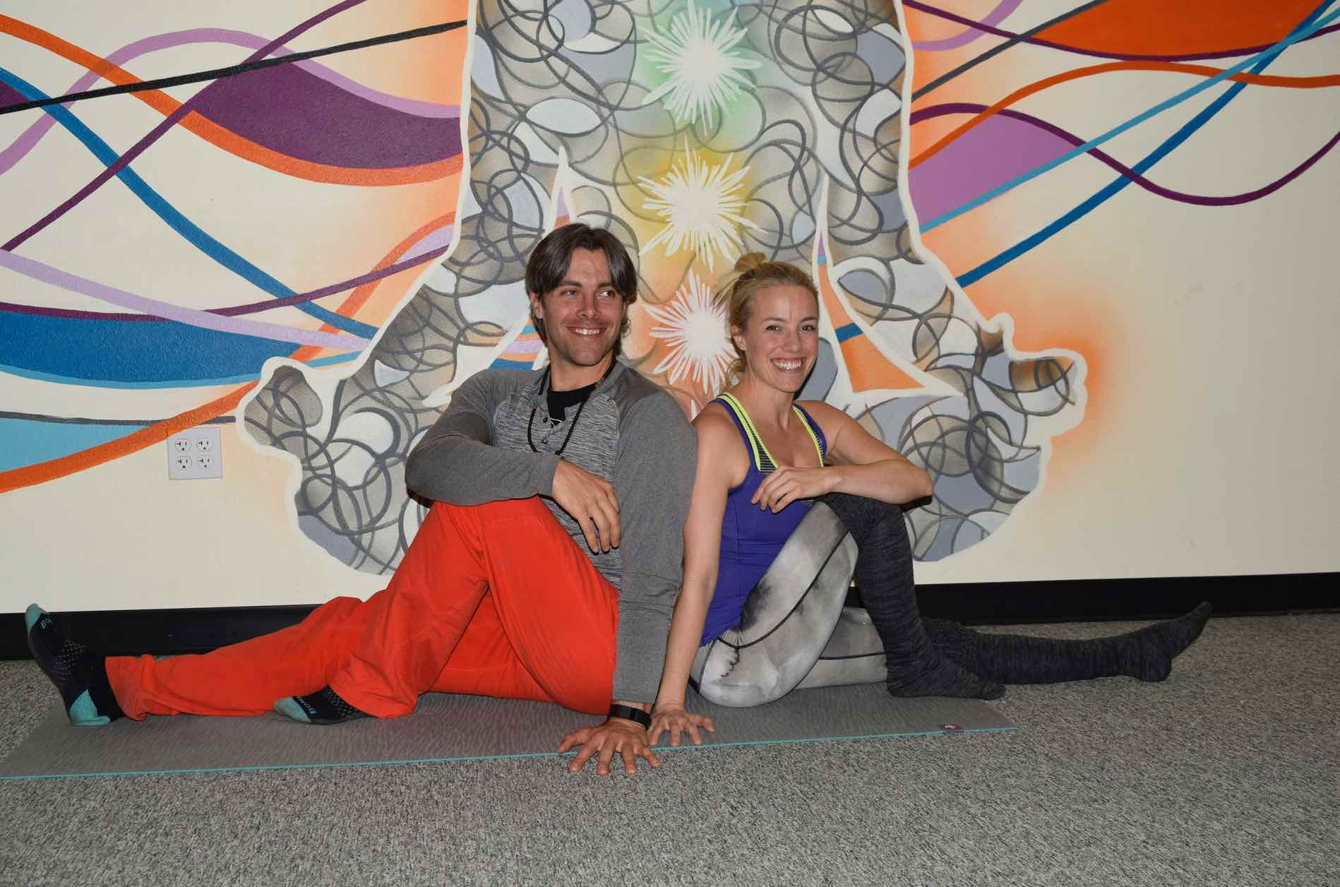 Photo of Amber and Austin Richman sitting in front of the Charka Mural