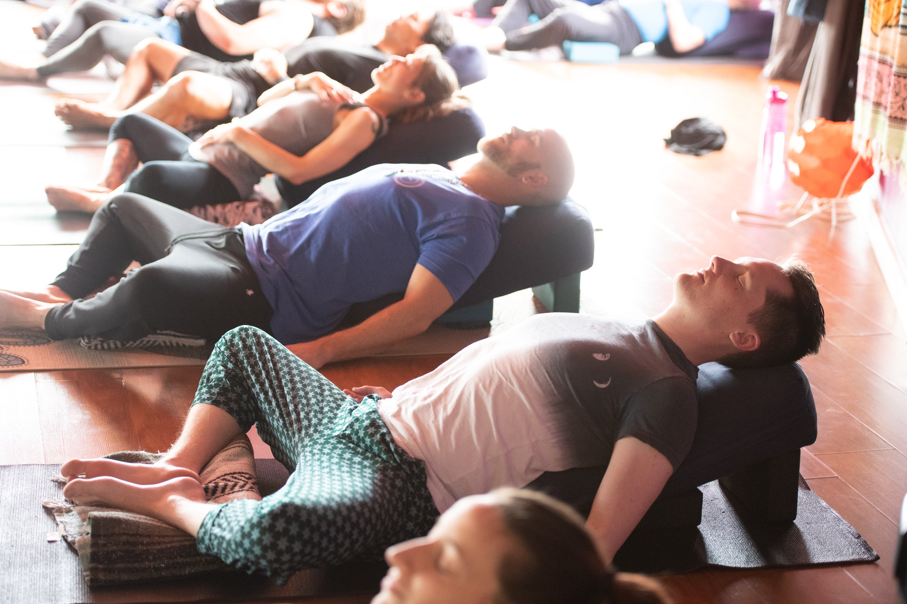 photo of men relaxing on yoga props in supta baddha konasana