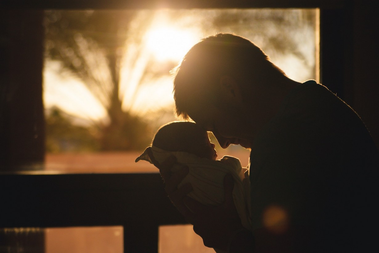 Photo showing the silhouette of a parent holding child