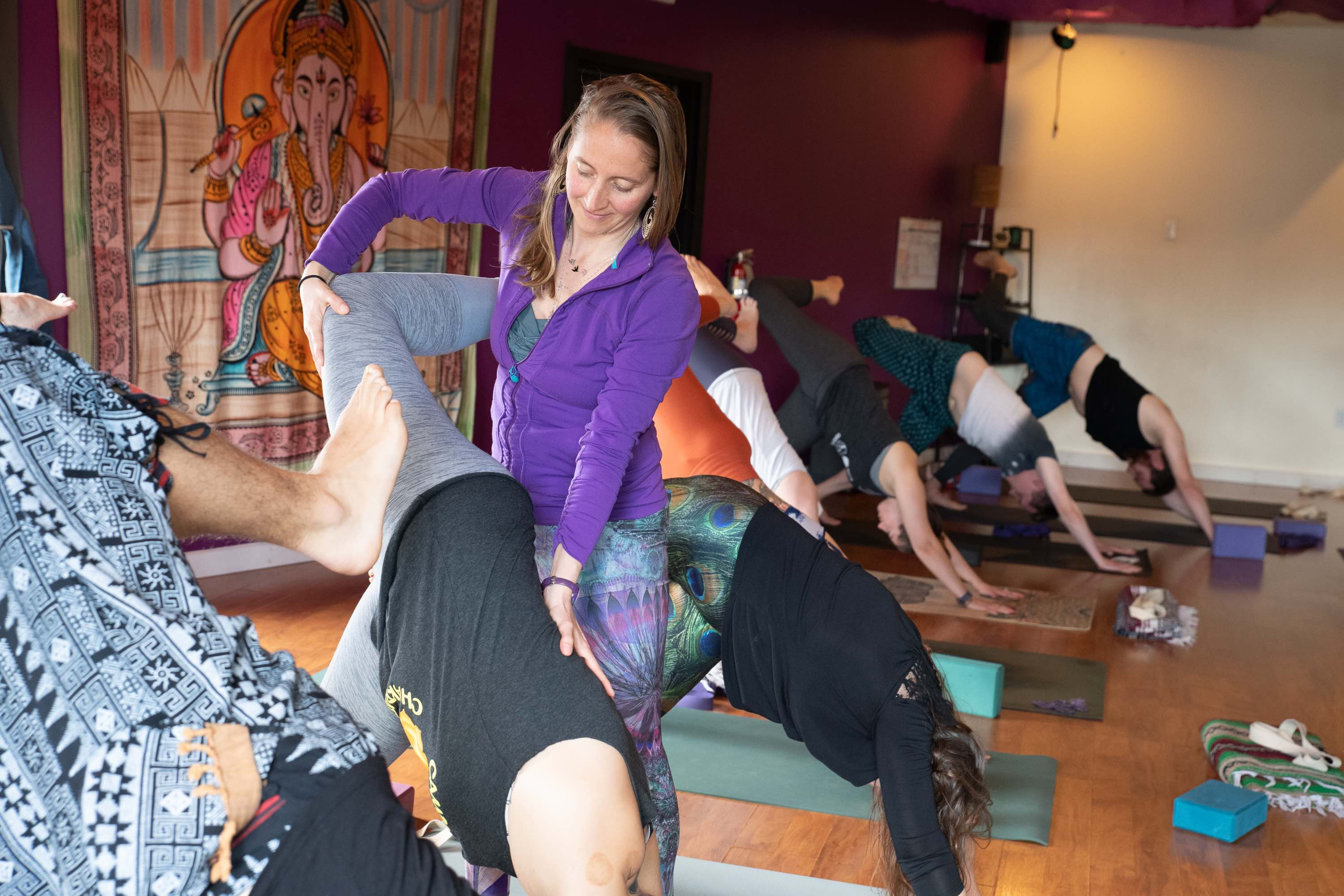 Teacher offers a hands-on adjustment in group yoga class