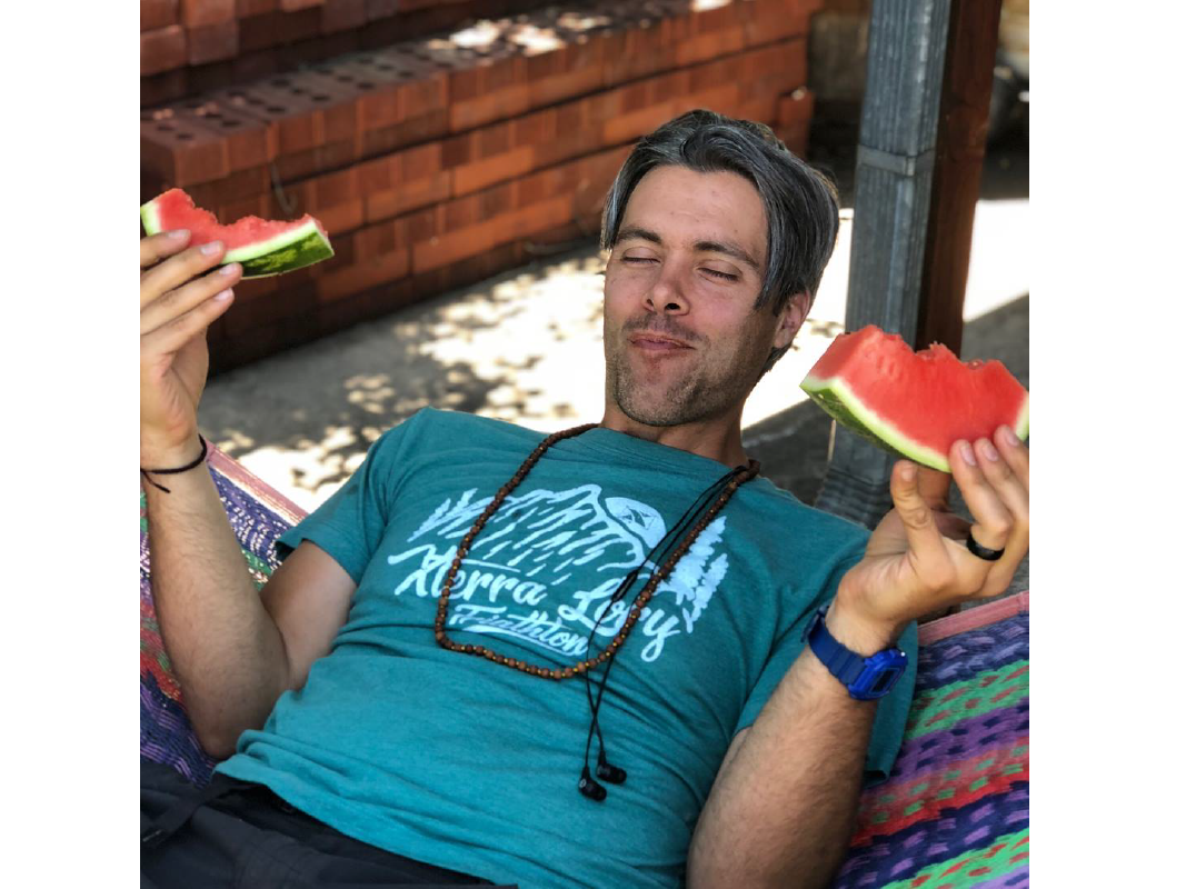 Photo of Austin eating watermelon on a hammock