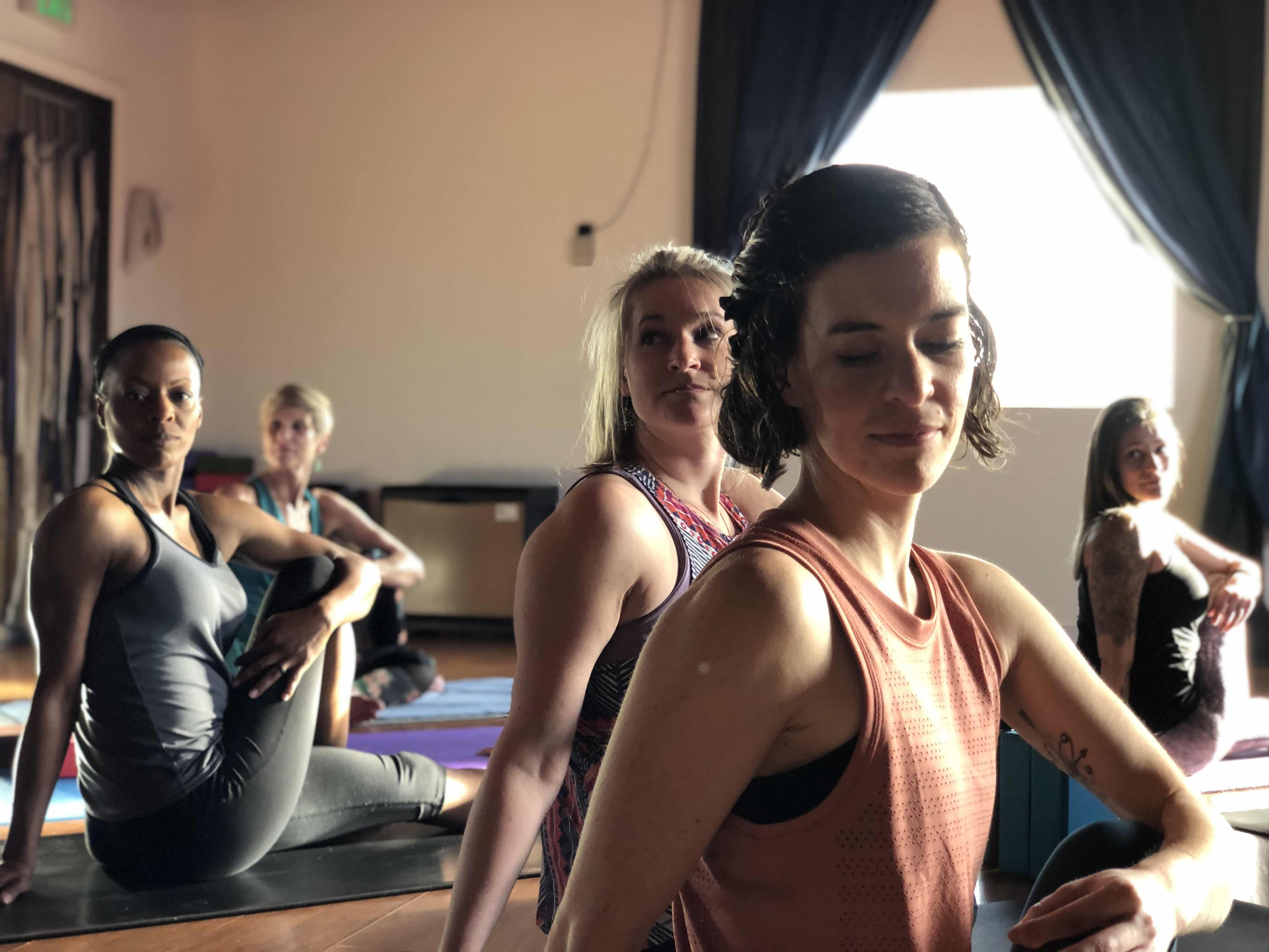 Photo of Erika in Ardha Matsyendrāsana with other students behind her