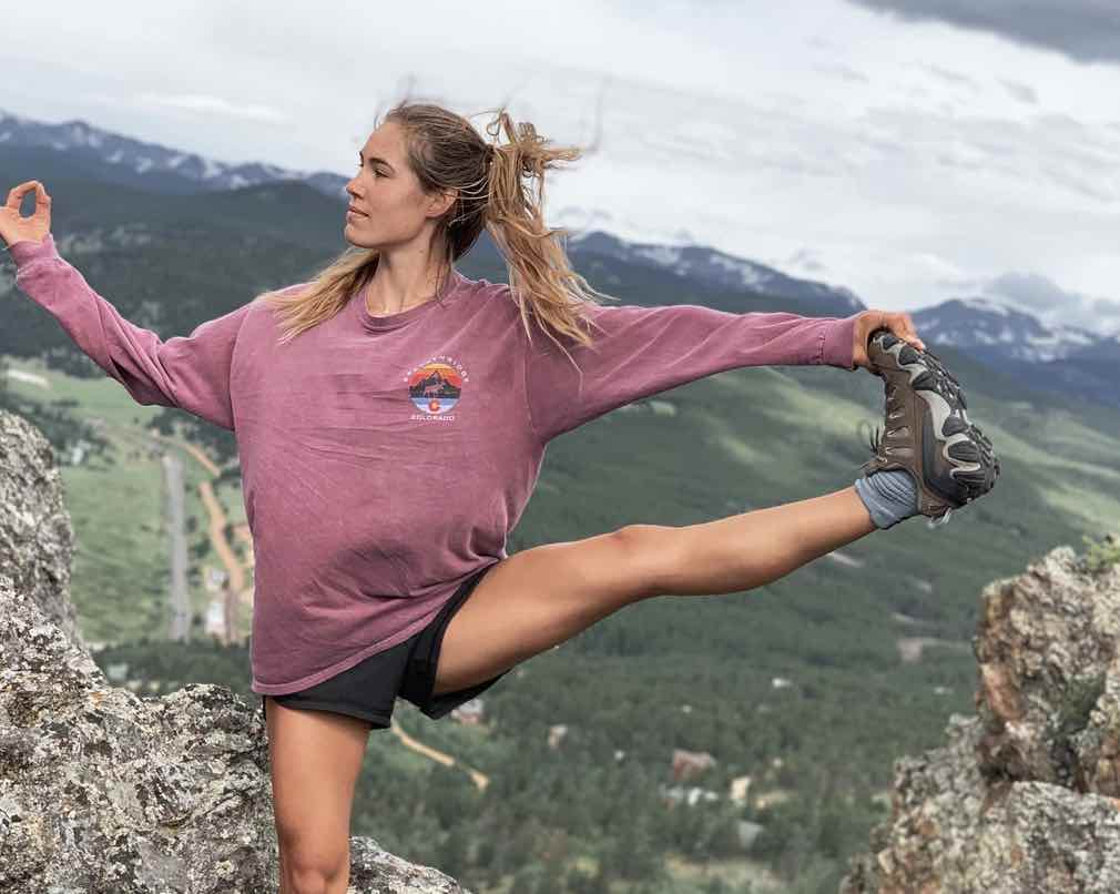 Photo of Jenn Urbaniak doing yoga in the mountains